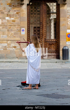 Female playing violin on the street of Florence in daytime. Musician plays the electronic violin. Sunny morning - Stock Photo