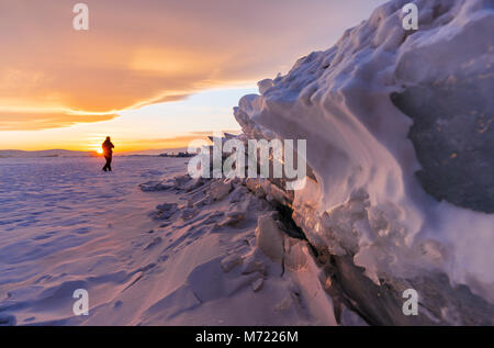Winter landscape in sunset, Cracked frozen ice of lake covered by snow at lake Baikal, Russia in sunset - Stock Photo