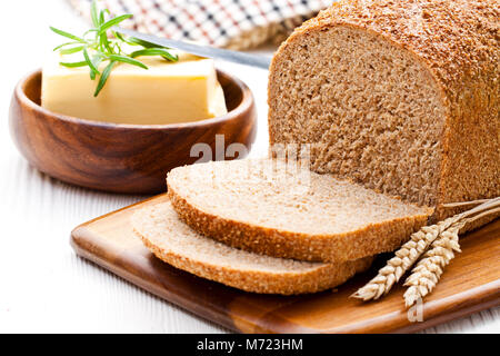 Sliced  slow-baked organic wholemeal bread with butter and rosemary and wheat ears - Stock Photo