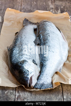 Close  up on a whole raw salmons wooden background - Stock Photo