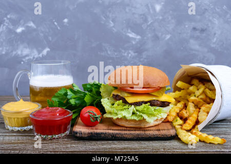 Juicy burger, french fries, sauces, beer  on a wooden background. Fast food. Street food. - Stock Photo