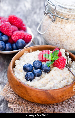 Porridge  in a wooden bowl with berries - Stock Photo