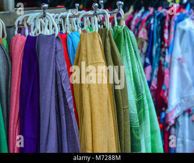 Selling textile (silk) at street market in Chinatown, Singapore. - Stock Photo