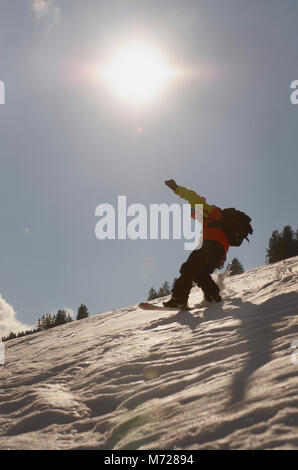 snowboarder riding in swiss alps - Stock Photo