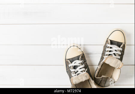 Old black sneakers on white wood background - Stock Photo