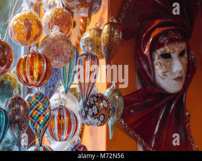 Colorful souvenirs from the famous murano glass. Venetian masks in store display in Venice. Annual carnival in Venice - Stock Photo