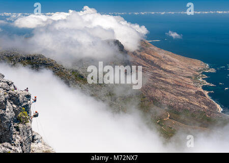 Abseilers abseiling off the summit of Table Mountain with Cape Town's Atlantic coastline in the background. - Stock Photo
