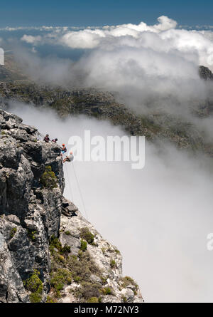 Abseilers abseiling off the summit of Table Mountain in Cape Town with the cloud-shrouded Twelve Apostles mountains - Stock Photo