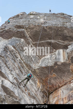 Abseilers and rock climbers just below the summit of Table Mountain in Cape Town. - Stock Photo