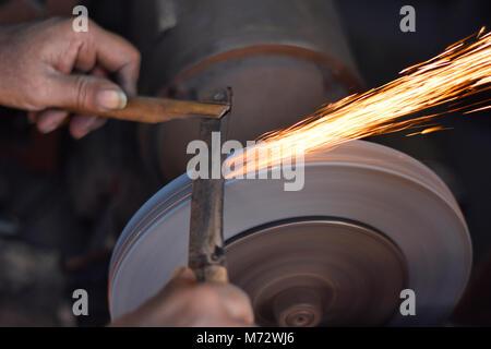 Man grinding on abrasive cutting and knife-sharpening stones. Mumbai, Maharashtra, India - Stock Photo