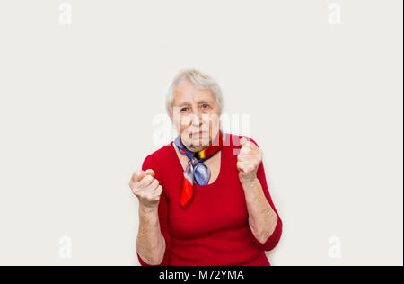 Angry old woman making fists on white background - Stock Photo