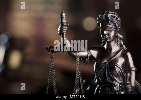 Law symbols on brown background. Statue of justice - Themis, gavel of judge and books. - Stock Photo
