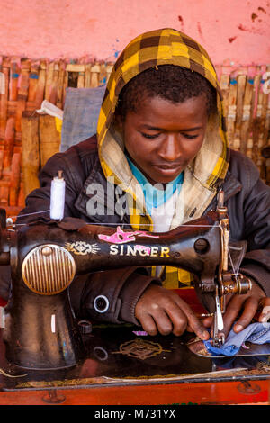 A Young Man Repairing Clothes Using An Old Fashioned Sewing Machine At The Saturday Market In The Dorze Village - Stock Photo