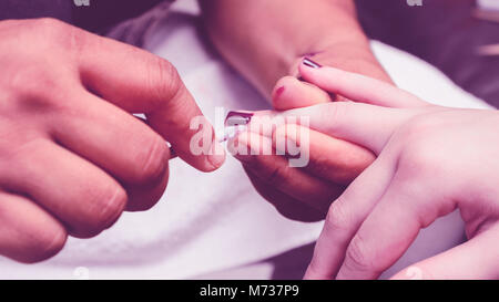 Manicurist removing the excess of ink from the polish nails after painting using a wooden stick with cotton on tip. - Stock Photo