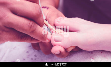 Manicurist removing the excess of ink from the polish nails from client feet after painting using a wooden stick. - Stock Photo