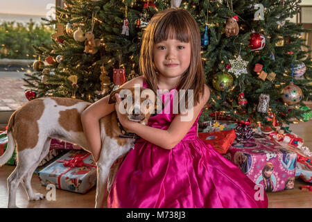 Five year old girl and her dog sitting under the Christmas tree - Stock Photo