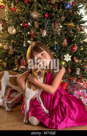 Five year old girl with her dog sitting under the Christmas tree - Stock Photo