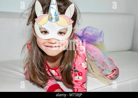 A six year old girl wearing a unicorn mask - Stock Photo