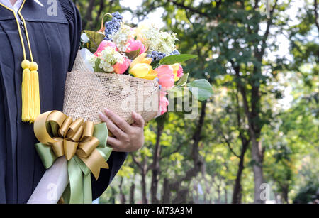 student graduate holding Flower bouquet in hand - Stock Photo