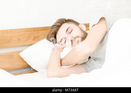 Men sleep on bed in the morning with in bedroom - Stock Photo