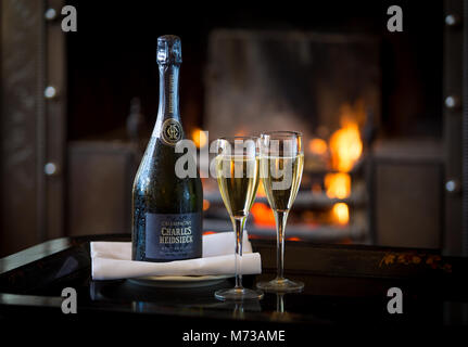 A Bottle of champagne with two filled glasses on a tray in front of a roaring log fire - Stock Photo