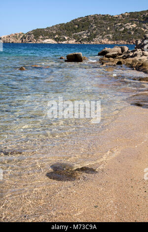 a view of the clear water of the Mediterranean sea in a quiet beach in the coast of Baja Sardinia, in the famous - Stock Photo