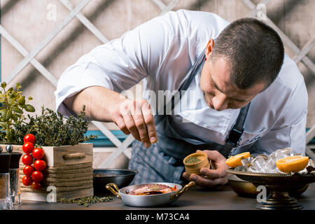 Chef sprinkling spices on dish from octopus in commercial kitchen. Gourmet Restaurant - Stock Photo