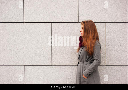 teenager brunette girl with long hair leaning against a wall - Stock Photo