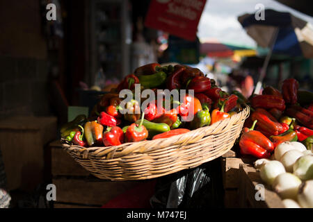 A basket piled with red and green peppers for sale at an outdoor Mayan farmer's market in San Cristobal Verapaz, - Stock Photo