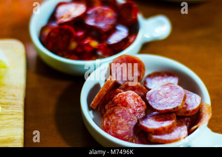 set of traditional Spanish sausages, side dishes of thinly sliced different chorizo, sets of meats, tasty meal - Stock Photo