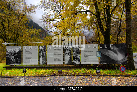 Trummelbach Falls information board in front of yellow maple trees - Stock Photo