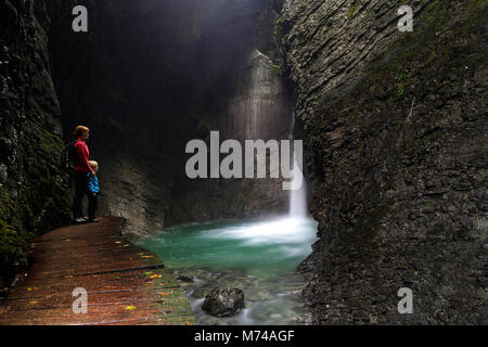 Mother and son standing on a wooden footpath and looking to gorgeous waterfall, hidden in rocky amphiteater with - Stock Photo