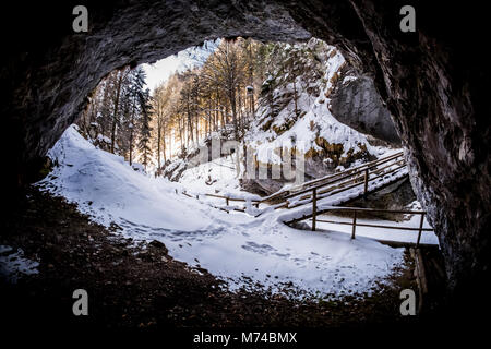 View from dark cave to snow covered gorge Baerenschuetzklamm with forest and wooden bridge in winter - Stock Photo