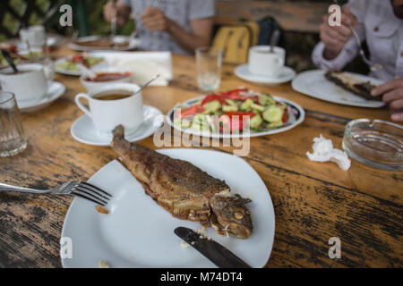 tasty river trout on a plate with vegetables in village restaurant dinner in Georgia - Stock Photo