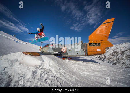 Snowboarding jump over plane in snowpark winter mountains in Italian Alps - Stock Photo