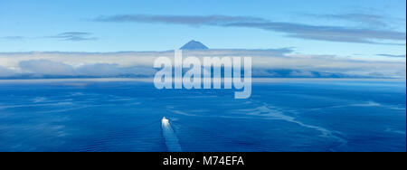 A boat crosses the sea between São Jorge island and Pico island on the horizon. Azores islands, Portugal - Stock Photo