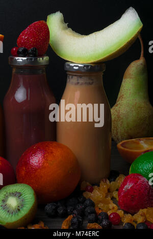 Freshly blended fruit smoothies of various colors with coconut milk and tastes in glass in wooden tray. Orange, - Stock Photo