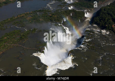 Aerial Pan Iguazu Falls, river, full waterfalls rainbow on border Brazil, Argentina, Paraguay UNESCO world heritage - Stock Photo