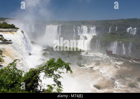 Aerial panorama Iguazu Falls waterfalls with perspective, tourists in mist on walkway, UNESCO world heritage site, - Stock Photo
