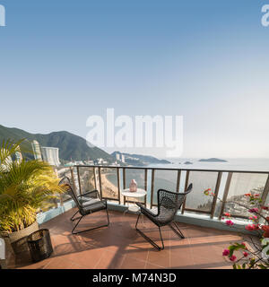 Table and chairs with a relaxing view over the beach from a balcony at Repulse Bay. Hong Kong. - Stock Photo
