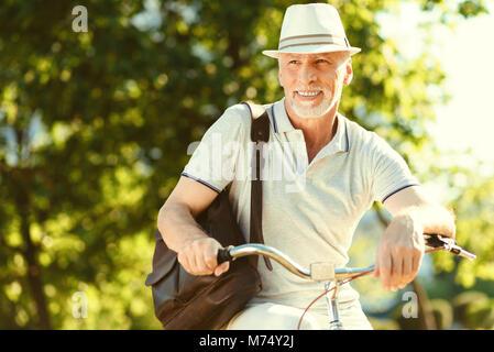 Happy aged man riding a bike - Stock Photo