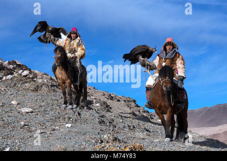 Kazakh brothers out hunting in the Altai Mountains of western Mongolia riding on their horses with their golden - Stock Photo