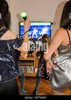 Vertical portrait of four girls dancing and singing together on their games console. - Stock Photo