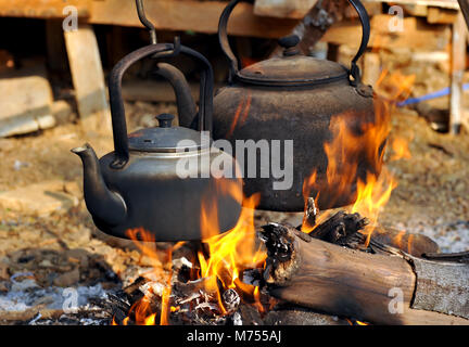Kettle pot on fire for boiling the water - Stock Photo