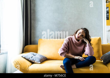 Picture of a tired unkempt woman lying on he couch at home. Girl watch TV new serial. Sofa relax concept after hard - Stock Photo