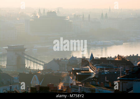Roofs and steeples of Buda and Pest sides of Budapest city divided by Danube river in mist - Stock Photo