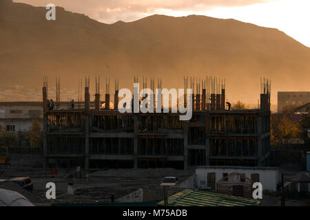 Construction workers framed by the setting sun with the Altai Mountains in the background on a hazy evening in Olgii, - Stock Photo