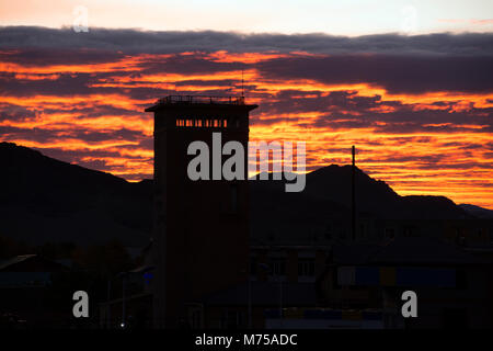 One of the tallest buildings in the western Mongolian city of Ölgii is silhouetted against the rising sun. - Stock Photo