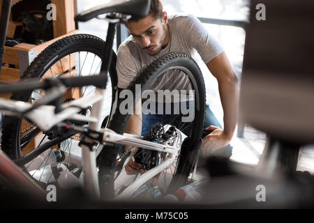 Man inspecting a bicycle wheel for alignment. Mechanic working on fixing a bicycle in workshop. - Stock Photo
