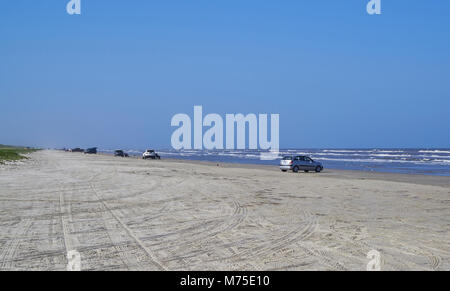 Cars, Trucks and SUV's line up on the white sandy Beach of Padre Island, near Corpus Christi in Texas. - Stock Photo